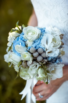 Невеста держит красивый свадебный букет
