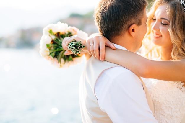 신부는 신랑을 껴안고 코 토르만의 부두에서 손에 꽃다발을 들고 클로즈업