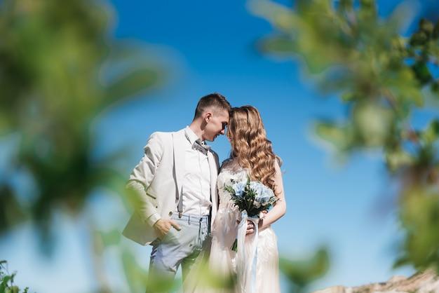 푸른 하늘에 대 한 가벼운 소송에서 신랑을 포옹하는 아름 다운 드레스의 신부. 낭만적 인 사랑 이야기.