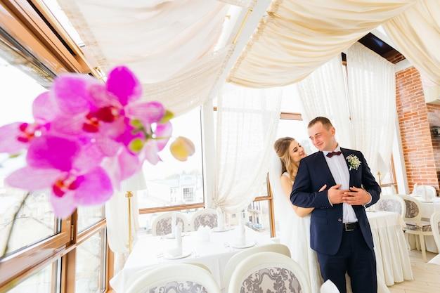 Невеста в красивом платье обнимает жениха с тыльной стороны зала ресторана.