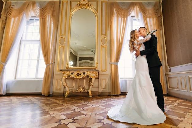Невеста в красивом белом платье держит свадебный букет, а жених обнимает ее и целует. комната с большим зеркалом и окнами.