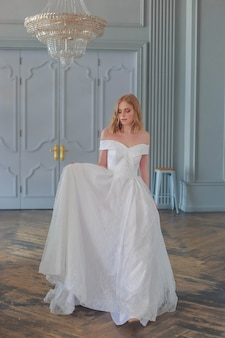 Невеста в красивом белом свадебном платье входит в зал, держась за подол платья.