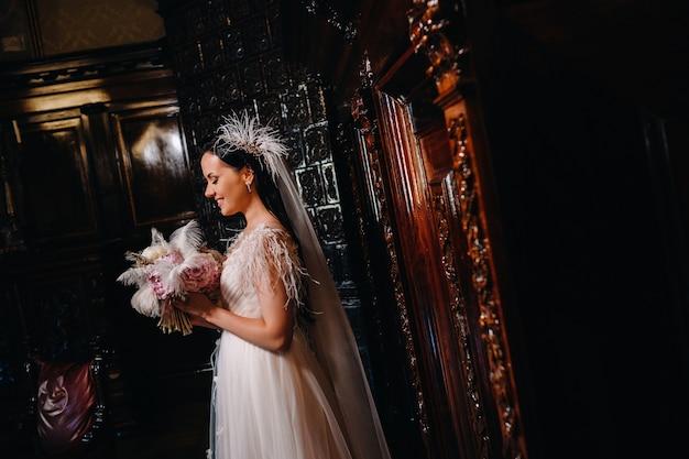 ウェディングドレスを着て花束を持った花嫁は、城の古い内部に立っています。