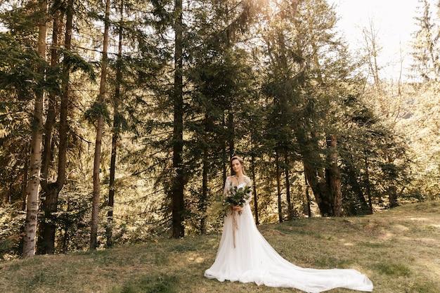 結婚式の花束を持って、白い美しいロングドレスの花嫁