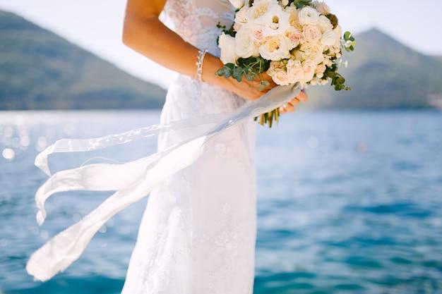 白いドレスを着た花嫁は、シーンで彼女の手にバラの美しいウェディングブーケを持っています