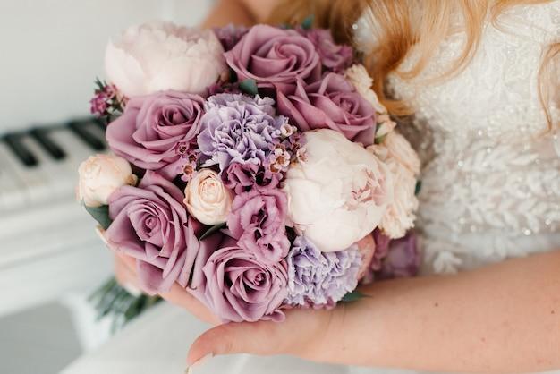 흰 드레스의 신부는 핑크 꽃 클로즈업의 꽃다발을 보유하고 있습니다. 혼례