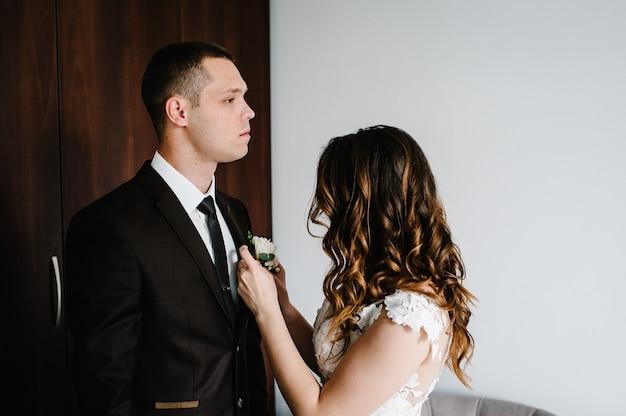 白いドレスを着た花嫁は、新郎を結婚式のブートニアのジャケットに着せます。結婚式のコンセプト。