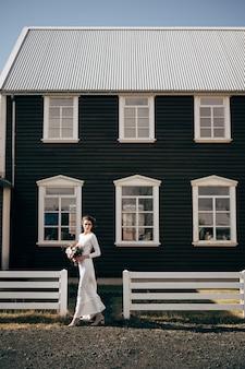 Невеста в белом платье с букетом в руках идет на фоне деревянных окон.
