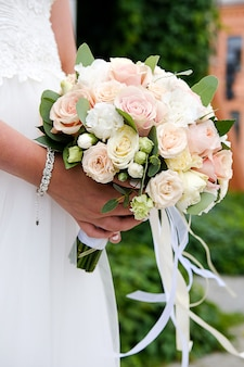 Невеста в белом элегантном свадебном платье держит красивый свадебный букет из разных цветов и зеленых листьев. свадебная тема. выборочный фокус.