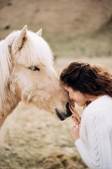 白いウェディングドレスの花嫁は、顔の目的地のアイスランドの結婚式で白い馬を撫でる