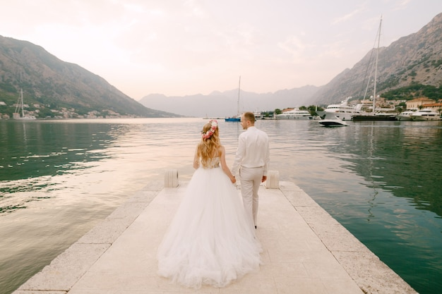 Невеста в венке и жених гуляют по пирсу, держась за руки возле старого города котор в