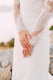 レースの袖のドレスを着た花嫁は、指のクローズアップに結婚指輪を付けて手を組んだ。