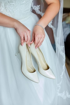 그녀의 웨딩 드레스의 신부는 집에서 그녀의 손에 그녀의 세련된 베이지 색 신발을 들고
