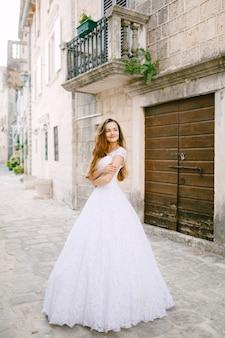 부드러운 웨딩 드레스를 입은 신부는 perast의 아름다운 고대 건물 근처에 서 있습니다. 고품질 사진