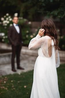 Невеста в саду стоит спиной к зрителю и смотрит на жениха