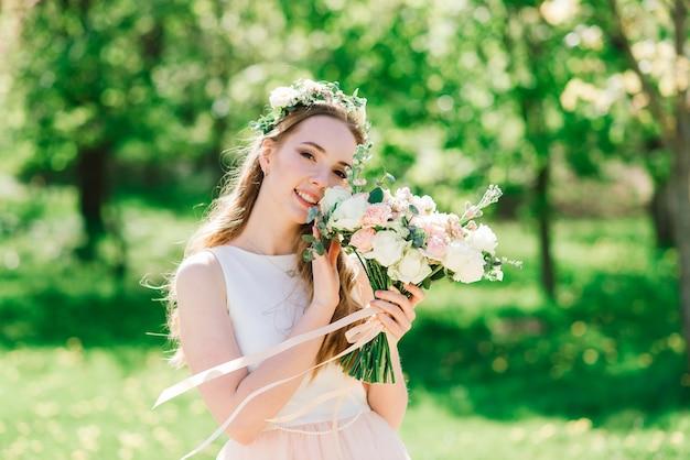 하얀 웨딩 드레스의 신부는 녹색 공원에서 꽃다발을 들고있다. 화창한 날에 여름 결혼식.