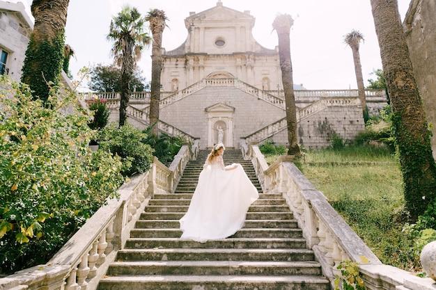화환의 신부는 prcanj의 뒷모습에서 고대 사원의 그림 같은 계단을 올라갑니다