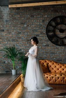 Невеста - брюнетка европейского вида. одиночный портрет. свадебный макияж и прическа. модель. утро невесты. будуар в отеле.
