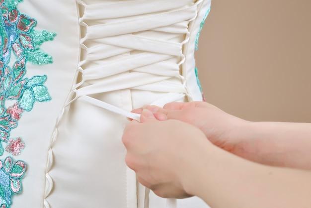 신부는 코르셋의 끈을 묶는 데 도움을 받습니다.