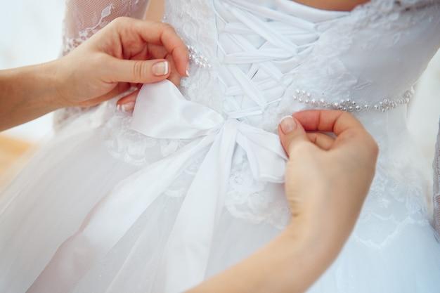 신부는 드레스를 입는 것을 돕습니다. 고급스러운 웨딩드레스. 최고의 결혼식 아침. 순백의 코르셋 드레스를 입은 신부의 뒷모습. 신부의 여자 친구