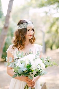 신부는 장미, 유칼립투스 가지, 섬세한 흰색 꽃과 어두운 열매의 웨딩 부케를 손에 들고 있습니다.