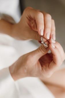 신부는 보석으로 약혼 반지를 손에 들고 있습니다.