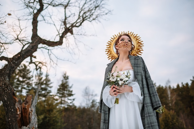 신부는 눈 덮인 숲에 서 있습니다. 멋진 보호 마스크를 쓴 신부.