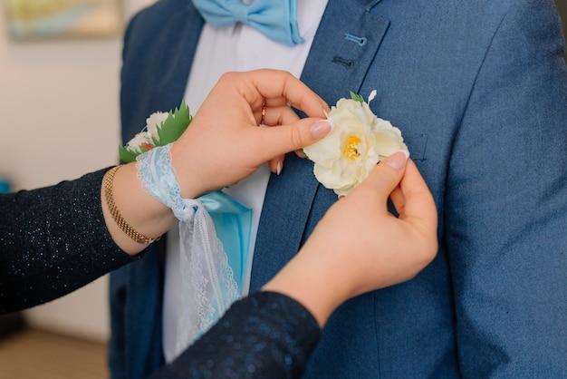 花嫁は新郎のブートニアを着ています。結婚式のための朝の準備新婚夫婦。結婚式のアクセサリー。