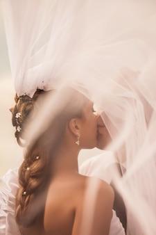 花嫁はベールの下で新郎にキスします花嫁の結婚式の髪型