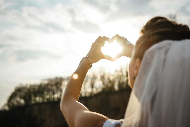 花嫁は閉じた手のひらを通して太陽をハートの形で見ています
