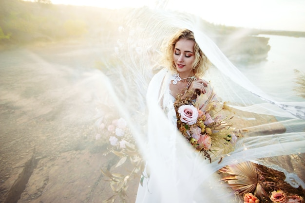 Невеста возле свадебного украшения на церемонии на скале у воды на закате. вуаль, летящая от ветра