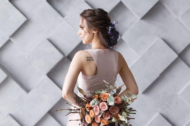 ウェディングドレスの花嫁、または若い女性が、カメラ付きブーケに戻って立っています。