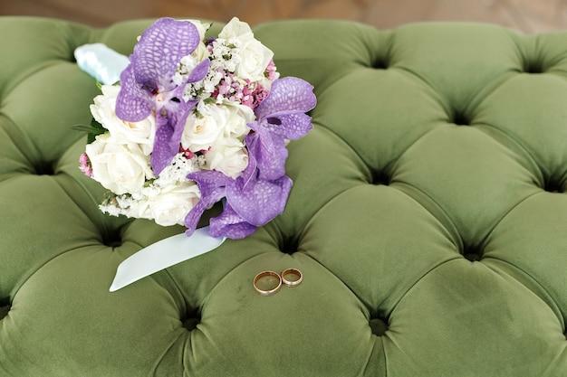 緑のソファに花嫁の花束と結婚式の金の指輪。閉じる