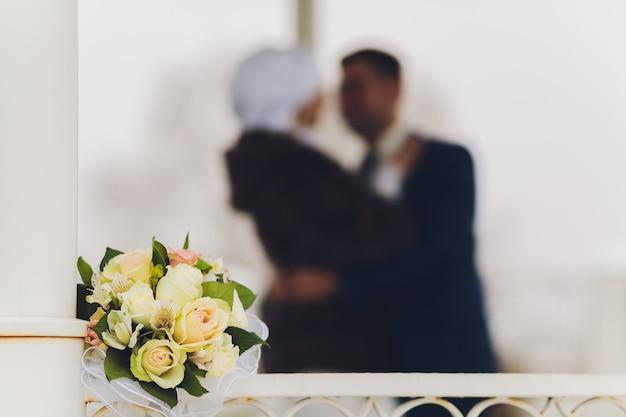 Букет невесты лежит на земле на фоне молодоженов.