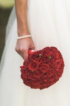 신부의 손에 빨간 장미 꽃다발, 흰색 드레스