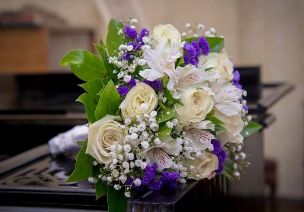 Букет невесты с белыми розами и фиолетовыми гвоздиками, лежащими на пианино крупным планом