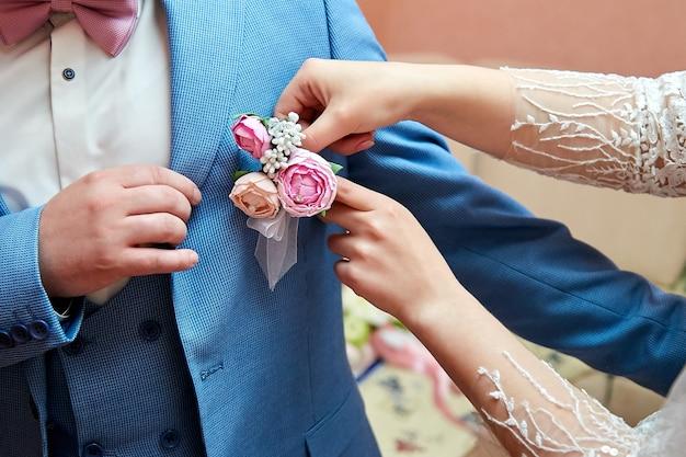 Рука невесты надевает бутоньерку на пиджак жениха.