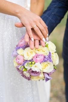 結婚指輪のある花嫁の手は、ウェディングブーケの背景にある新郎の手にあります。花嫁の花束の背景に新婚夫婦の手