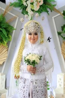 花嫁の肖像画は伝統的なジャワとイスラム教のドレスを着ています