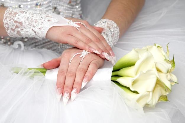 신부는 손질된 손을 보여줍니다. 패션과 여성의 아름다움