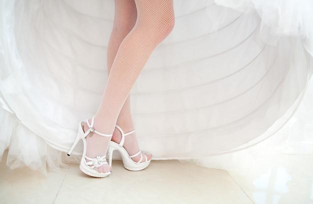 花嫁は白い結婚式の靴を示しています