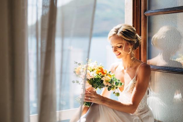 花嫁は海の景色と羽ばたきカーテンのある開いた窓に座って、ウェディングブーケを持っています