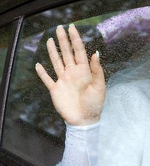 車の中で座っている花嫁は、雨の間に霧のかかった窓ガラスに手を置いた