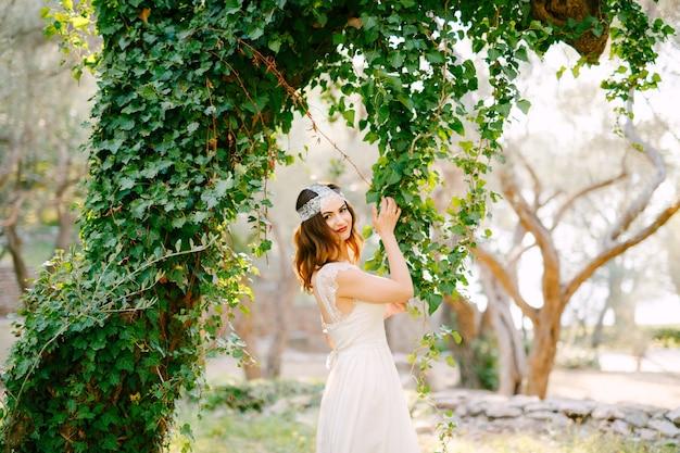 Невеста стоит возле красивого дерева, увитого плющом, и трогает висящий плющ в живописном парке. фото высокого качества