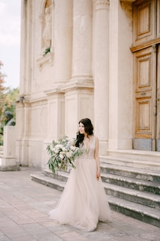 Невеста стоит у дверей старинной церкви с букетом пионов и белых роз.