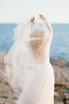 신부는 팔을 뻗은 채 바위 해변에 서 있습니다.