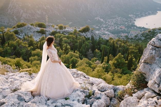 Невеста стоит на вершине горы с панорамным видом на залив.