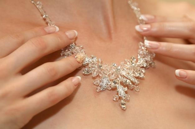 신부는 목에 장신구를 곧게 편다. 여성복의 아름다움과 패션