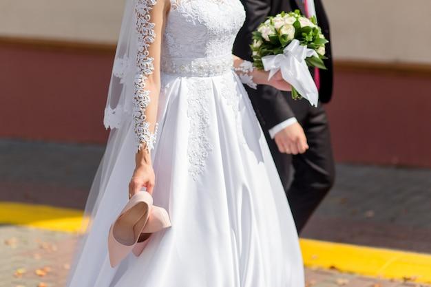 Невеста сняла неудобную обувь и гуляла босиком с женихом по улице.