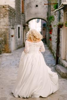 Невеста гуляет по красивой узкой улочке старого города пераста с кирпичными домами сзади.